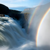 Iceland, Arnessysla County, Rainbow forms as Hvita River pours over Gullfoss waterfall on summer morning