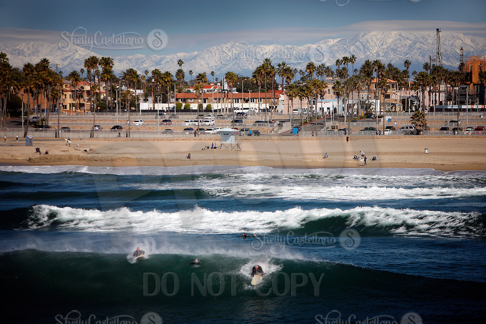 26 January 2008:   View of Surf City, Huntington Beach located in Southern California in Orange County on a beautiful day between winter storms.  Surfers in the water and snow on the mountains surrounding Orange and Los Angeles Counties on a winter Saturday afternoon.