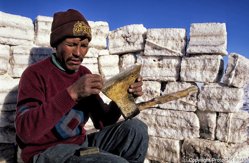 Inocencio  Flores  it sharpens an axe in a coat constructed by blocks of salt .  Salar de Uyuni ( Uyuni salt flat ) . Department  of Potosí  ( Los Lipez).  South West  Bolivia. <br /> Adult Altiplano America Andes Arid  Aridity Axe Barren  Bicycle Block  Bolivia Cleaver Color Colour Cone  Day Daytime  Department  Desert Desolate Desolation Dry  Exterior Extraction  Geography Hack Hard Hatchet  Heat Highlands  Horizontal  Human  Latin America Lake  Lined Los Lipez Male Man Men Miner Mining Nature  Resource  Natural  One Outdoors Outside  Pan People  Person Pyramide Potosí  Production  Region Resource Rural Salar de Uyuni  Salt Flat  Salt Pan  Salt lake  Scenic Seasoning  Single Shape South America  Southwest  Sud Sunglasses  Surface Travel  l West White Work  Worker Working