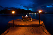 A dinner table sits on the end of pier in the evening on Song Saa island.