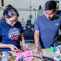 Wynona Wilson, left, disassembles a tiny air motor as  Shane Tsosie looks on at Navajo Technical University manufacturing lab in Crownpoint Thursday.