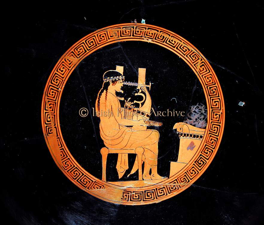 Red-figured kylix (drinking-cup) showing a youthful Apollo seated at an altar with a stringed instrument known as a kithara. Greek, made in Athens about 480-470 BC. The kithara was stringed instrument heavier and more solemn in tone than the lyre. Professional singers (kitharodes) used it to accompany their performances.