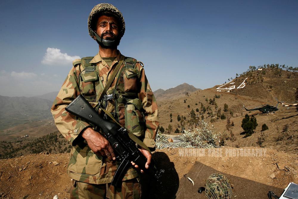 A Pakistani soldier stands guard at a military outpost on a strategic mountain-top overlooking Mingora on Monday, February 25, 2008, Swat Valley, Pakistan. The Pakistan Army has spent more than three months battling Islamic militants in the Swat Valley, reclaiming large swaths of land, but failing to drive completely the militants from its mountainous landscape. Once a major tourist destination, the Swat valley was overrun last year with Islamic militants intent on imposing hard-line Islamic rule. In November, 2007, the military staged one of its largest operations since its six-year involvement in the war on terror to drive the militants out. Pakistan's ongoing commitment to fighting Islamic militancy and terrorism is unclear with the formation of a new government after recent national elections. (Photo by Warrick Page)