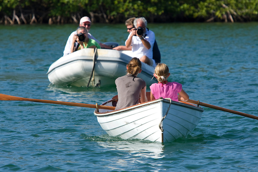 Photographers take photographs of competitors during a rowing dinghy race  during the 2008 Antigua Classic Yacht Regatta . This race is one of the worlds most prestigious traditional yacht races. It takes place annually off the cost of Antigua in the British West Indies. Antigua is a yachting haven, historically a British navy base in the times of Nelson.