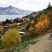 Mountain Bike racers tackle the Ben Lomond Forest course high above Queenstown during the Outside Sports Super D Enduro event in Queenstown, Central Otago, at the Weekend. The 6 hour non stop team and individual races attracted 86 competitors and included Skyline Gondola access. The event was part of the inaugural Queenstown Bike Festival, taking place from 16th-25th April. The event hopes to highlight Queenstown's growing profile as one of the three leading biking centres in the world. Queenstown, Central Otago, New Zealand. 16th April 2011. Photo Tim Clayton..