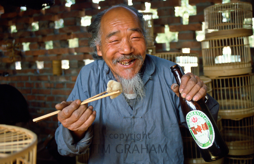 Market trader selling bird cages stops for a beer and his lunch using chopsticksduring a break in Peking (Beijing) China