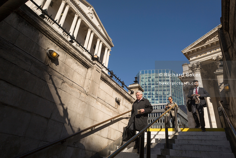 A woman and businessmen descend the steps leading down into Bank Underground station, beneath the Bank of England and neo-classical pillars of Royal Exchange in the City of London - the capital's financial centre (aka The Square Mile), on 27th September 2018, in London, England.