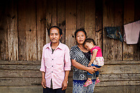 Wa Meng Ha, and his wife and youngest daughter at their home in Khon Kahndone Village, Laos.