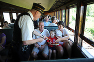 LANSDALE, PA - AUGUST 24: Conductor Wayne Whiteley  (L) of Langhorne, Pennsylvania collects tickets from Tom Borneman, Jackson Headly, 4, and Kathy Boreman of Lansdale, Pennsylvania aboard the New Hope and Ivyland Railroad during Founders Day August 24, 2013 in Lansdale, Pennsylvania. The New Hope and Ivyland Railroad made special trips as part of Founders Day from Lansdale to Souderton. (Photo by William Thomas Cain/Cain Images)