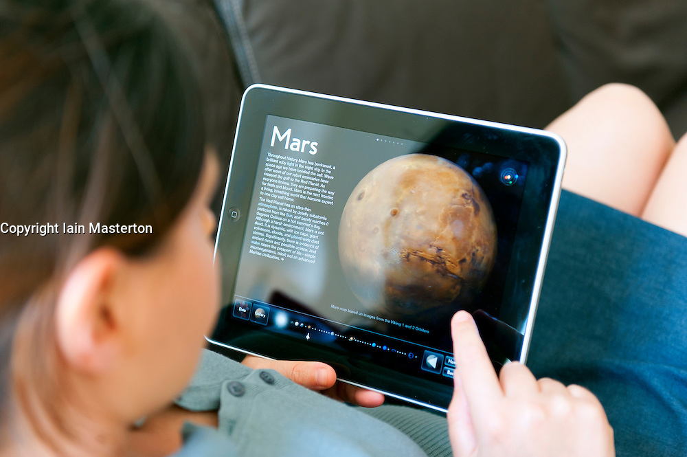close up of woman using iPad digital tablet computer using interactive app on Solar system