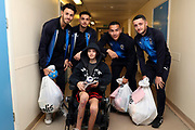 AFC Wimbledon defender Will Nightingale (5), AFC Wimbledon attacker Egli Kaja (21), AFC Wimbledon defender Rod McDonald (26), AFC Wimbledon midfielder Anthony Hartigan (8) delivering Christmas presents to the children on behalf of AFC Wimbledon, at St George's Hospital, Tooting, United Kingdom on 13 December 2018.