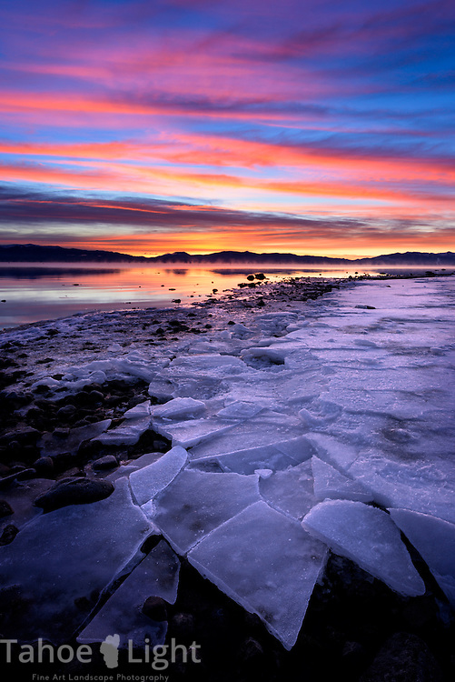 Sunrise over frozen ice on the shores of Lake Tahoe in winter.