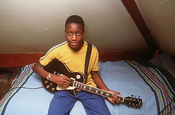 Teenage boy sitting on bed in bedroom playing electric guitar,