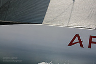 State-of-the-art genoa jib and hull of France's Areva Challenge yacht gleam in afternoon sun at America's Cup fleet race; Valencia, Spain.