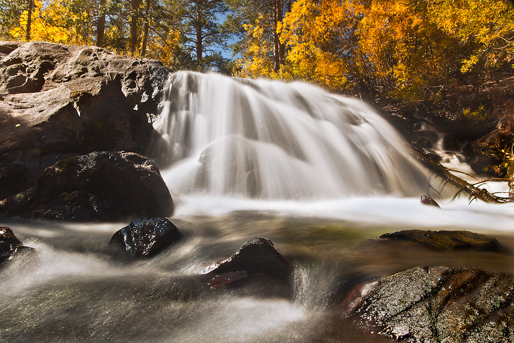 softly flowing waterfall in lee vining canyon, california during the peak of fall foliage.