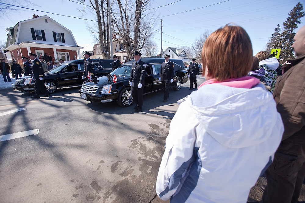 Residents line the streets to pay their respects to fire fighters Kenneth Rae and Raymond Walter during a funeral procession for the men in Listowel Ontario, Thursday, March 24, 2011. The men were killed fighting a blaze in a dollar store last Thursday when the roof collapsed.<br /> THE CANADIAN PRESS/ Geoff Robins
