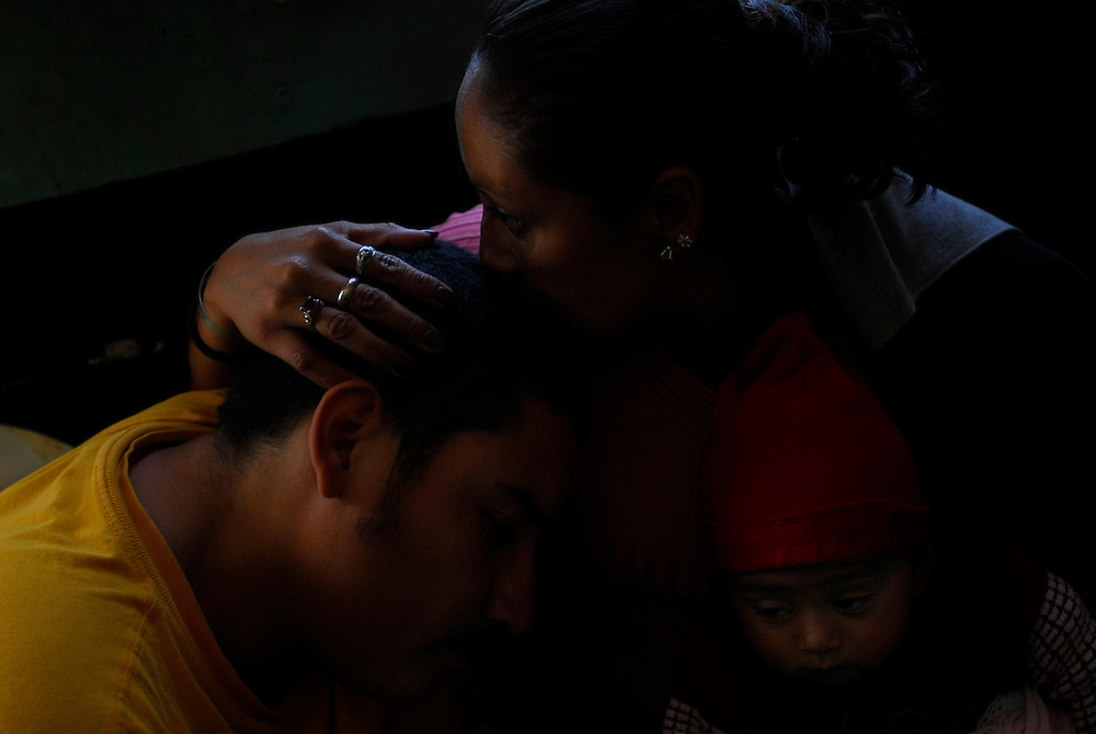 "Neddie Hiron Rodriguez, left, gets a kiss from his wife Maria during a family visit wih their child Maria at Casa Hogar, a rehabilitation home for alcohol and drug addicts, outside of Antigua, Guatemala. Rodriguez has been a patient at Casa Hogar for nearly a month now...Casa Hogar currently houses 44 men (with a maximum of 60.) Jorge Rosales, himself a former drug user, founded the home 2 years ago after he kicked his habit and left the garbage dump he had been living in for thirteen months...If accepted into Casa Hogar the voluntary residents must first spend 6 days in a first floor room of mattresses, are denied showers and must eat meals separately from other residents. Patients in the first floor zone suffer from convulsions, vomiting and other withdrawal symptoms and are monitored round the clock by a nurse. Most alcoholics who enter the program have been drinking rubbing alcohol, according to Rosales, because it is so inexpensive...""If they make it"" says resident Byron Rosales, ""they can join us up top."" It is up to the individual when they feel they are ready to leave the home."