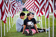 "10 SEPTEMBER 2011 - TEMPE, AZ:     KYLYNN TOM, 12, from SanTan Valley, AZ, her aunt, ALANA SMITH, from Gilbert, AZ, and brother, DAMON TOM, 14, sit in the Healing Field in Tempe, AZ, Saturday.  The ""Healing Field,"" a display of 2,996 flags, one for each person killed in the September 11 terrorists attacks on the World Trade Center in New York City and Washington DC, have become an annual tradition in Tempe, AZ. The event is sponsored by the National Exchange Club.     PHOTO BY JACK KURTZ"