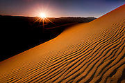 The setting sun casts dramatic shadows on the sand dunes in Dearth Valley National park, California