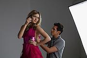 Model on Cell Phone While Designer Adjusts Dress