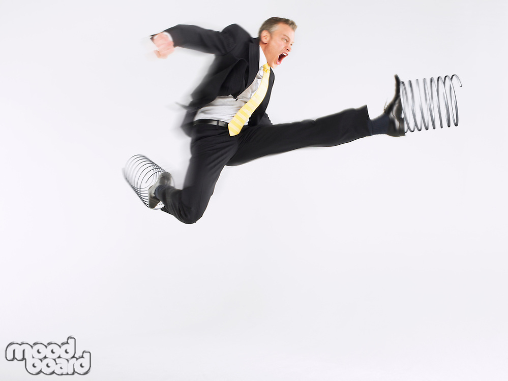 Business man jumping with springs on feet