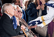 Rear Admiral Linnea Sommer-Weddington, right, presents  flags to family members during the committal service for Navy Radioman 2nd Class Quentin Gifford at Fort Snelling National Cemetery in Minneapolis May 12, 2018. (Courtney Perry for MPR)