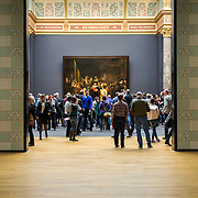 AMSTERDAM, NETHERLANDS - FEBRUARY 08: Visitor at Rijksmuseum admiring 'Night Watch', By Rembrandt Harmensz. van Rijn, on February 08, 2015 in Amsterdam. The Rijksmuseum is located at the Museum Square, and first opened its doors in 1885.
