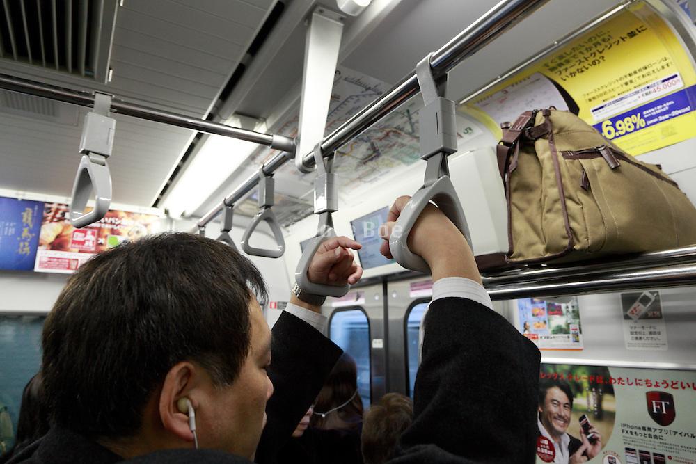 tired Japanese businessman commuting