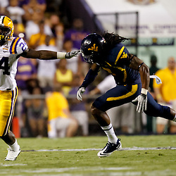 Sep 25, 2010; Baton Rouge, LA, USA; LSU Tigers running back Alfred Blue (24) runs away from West Virginia Mountaineers cornerback Robert Sands (2) during the first half at Tiger Stadium.  Mandatory Credit: Derick E. Hingle