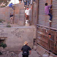 Undocumented migrants gather along the U.S.-Mexico border in San Diego, California. Please contact Todd Bigelow directly with your licensing requests. <br />