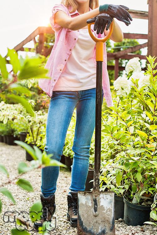 Portrait of gardener leaning on shovel in shop