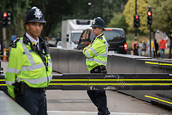© Licensed to London News Pictures. 15/08/2018. London, UK. Police stand next to a security barriers outside the Houses of Parliament, where a car crashed on Tuesday 14 August 2018 after hitting several cyclists. The driver, named as 29-year-old Salih Khater, is being held on suspicion of terrorism. Photo credit: Rob Pinney/LNP