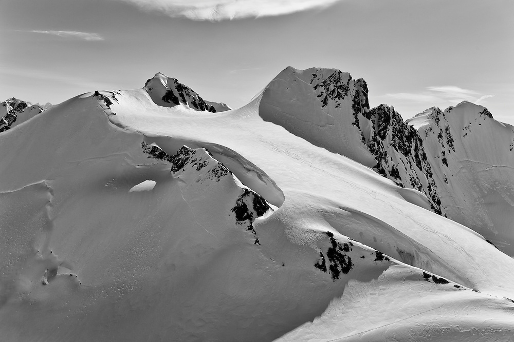 Covered in hundreds of feet of snow, this slope in the Chugach Mountains in Chugach State Park near Anchorage in Southcentral Alaska shows evidence of being skied by outdoor enthusiasts. Spring. Morning.