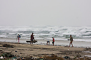 The beach of Vinh Loc on a rainy day. A typhoon out at sea makes the waves go high. People are collecting useful things landed by the surf.