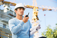 Male architect with blueprints using walkie-talkie at construction site