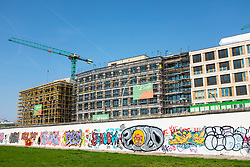 View of original section of Berlin Wall with new office buildings under construction to rear at East Side Gallery in Friedrichshain, Berlin, Germany. Property development in Berlin is booming at present due to rising cost of real estate and land.