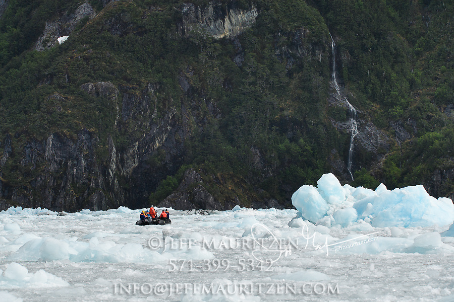 Expedition travelers aboard zodiac inflatable boats cruise through glacial ice in Garibaldi fjord in Parque Nacional Alberto de Agostini, Chile.