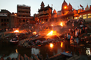 Bodies arrive day and night from far and near to be cremated at Jalasi Ghat, the cremation grounds at Manikarnika Ghat in the city of Varanasi, India. One hundred or more times a day male family members carry a loved one's body through the narrow streets on a bamboo litter to the Ganges River shore?a place of pilgrimage for Hindus during life, and at death. Not every Hindu can be cremated here, because of transportation costs and logistical considerations. Sometimes a body is burned in one location and the ashes brought to Varanasi. A ghat is a stairway in India leading down to a landing on the water.