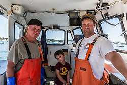 Captain Johnny McCarthy (right), his son Jack and father Mark, aboard the 'Isabella - Jack' at the Vinalhaven Fishermen's Co-op in Vinalhaven, Maine.