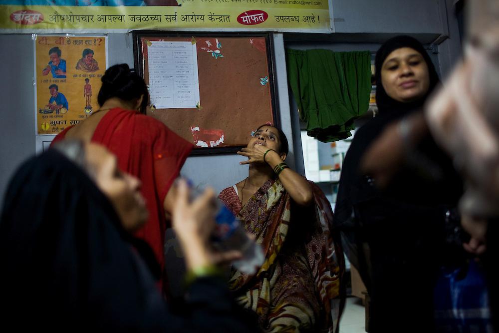Vanita Chaudhary(center) takes her daily medication with other TB patients at the Mahatma Nagar DOTS Center run by Maharashtra Janavikas Kendra, a local NGO.