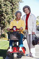 Senior woman on motor scooter on urban street with friend