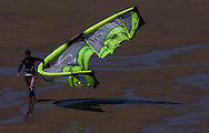 A kitesurfer floats his kite along the beach. (Photo © Jock Fistick)