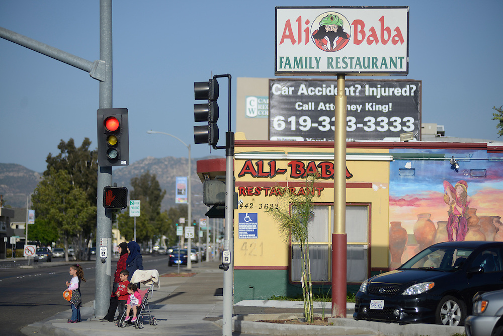Iraqi women waiting to cross the street with their children in front of the Ali Baba Family Restaurant. A small community of Iraqi refugees settled in the San Diego area during the aftermath of the 1991 Gulf War. The community has drawn many of the 11,000 Iraqi refugees who have been arriving in the area since 2007 when the United States first began admitting refugees fleeing the conflict in Iraq. Following two tragic wars involving the US and Iraq, Iraqi culture is gradually becoming part of the American landscape. El Cajon, CA. 01/05/2013.