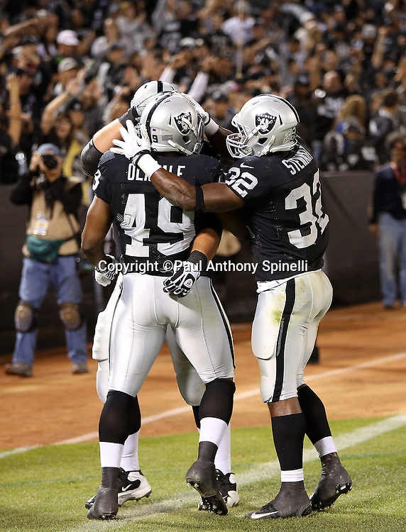 Oakland Raiders running back Jamize Olawale (49) celebrates with teammates after catching a 5 yard touchdown pass that cuts the Chicago Bears fourth quarter lead to 34-26 during the NFL preseason week 3 football game against the Chicago Bears on Friday, Aug. 23, 2013 in Oakland, Calif. The Bears won the game 34-26. ©Paul Anthony Spinelli