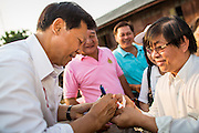 17 FEBRUARY 2013 - BANGKOK, THAILAND:  Pheu Thai gubernatorial candidate PONGSAPAT PONGCHAREON signs autographs for voters in Bangkok Sunday. Pol General Pongsapat Pongcharoen, a former deputy national police chief who also served as secretary-general of the Narcotics Control Board is the Pheu Thai Party candidate in the upcoming Bangkok governor's election. (He resigned from the police force to run for Governor.) Former Prime Minister Thaksin Shinawatra reportedly recruited Pongsapat. Most of Thailand's reputable polls have reported that Pongsapat is leading in the race and likely to defeat Sukhumbhand Paribatra, the Thai Democrats' candidate and incumbent. The loss of Bangkok would be a serious blow to the Democrats, whose base is the Bangkok area.     PHOTO BY JACK KURTZ