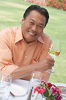 Smiling Man Enjoying a Glass of White Wine