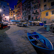 Late at night, the tiny harbour in the Cinque Terre village of Riomaggiore holds a few fishing boats while the town sleeps