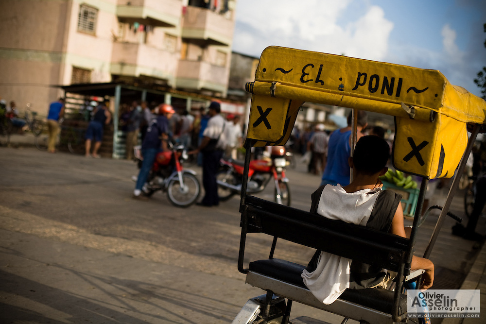 "The driver of a bicycle taxi named ""The Pony"" rests in his vehicle in Baracoa, Cuba on Sunday July 13, 2008."
