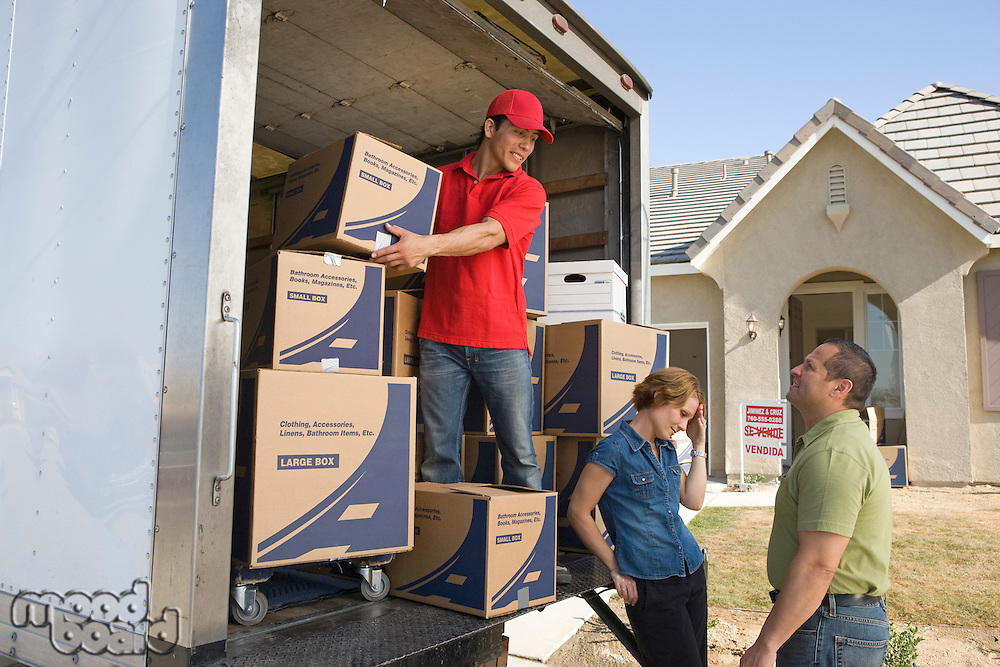 Man and couple unloading truck of cardboard boxes