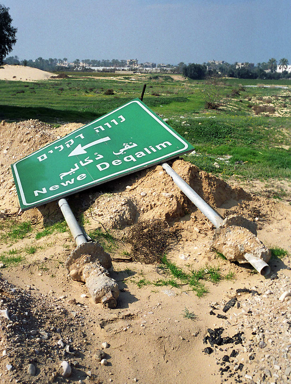 Road sign point to Newe Deqalim settlment on the ground